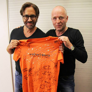 myRockworld memorabilia: Al Di Meola with The myRockworld UNIKAT Special BLING T-Shirt - front signed by Herman Rarebell (Scorpions), John Parr, Bobby Kimball (Toto), Jon Hiseman, Dave Greenslade, Clem Clempson, Barbara Thompson, Chris Farlowe (Colosseum), Al Di Meola, etc.